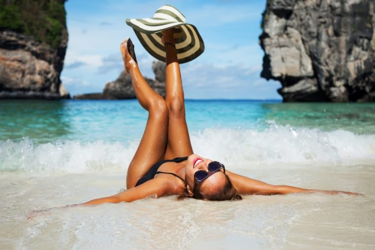 Summer lifestyle portrait of happy pretty young woman with tanned sexy body. Enjoying life and lying in the clear sea water on the beach of the tropical island. Stylish wide brimmed hat. Leg up