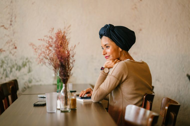 Portrait of a young Muslim woman. She is of Asian descent (Arab, Malay, Asian) and is wearing a turban (hijab, head scarf) and is smiling as she sits at a wooden table with flowers with her devices.