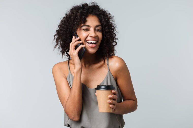 Happy young african woman casually dressed standing isolated over gray background, talking on mobile phone, holding takeaway cup of coffee