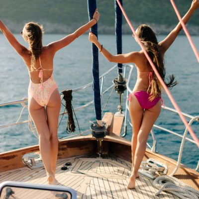 joyful women yachting. Two sexy women sail on yacht vacation