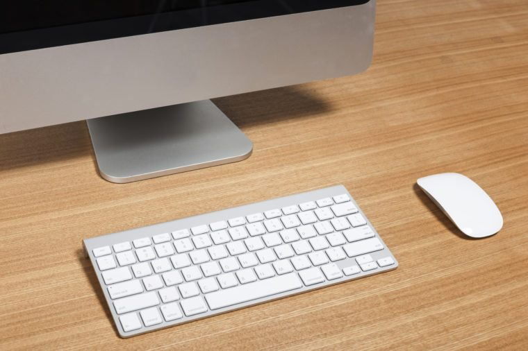 A aluminum(grey) desktop personal computer(PC) with wireless keyboard, mouse on the wood table(desk) isolated white.