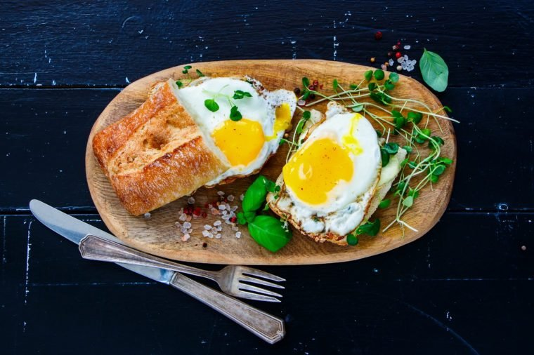 Close up of tasty rural breakfast toast with fried eggs and sprouts on wooden board over black grunge background, top view. Healthy, clean eating, dieting food concept