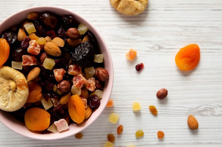 Dried fruits and nut mix in a pink bowl on a white wooden table, top view. Overhead, from above, flat lay. Close-up.