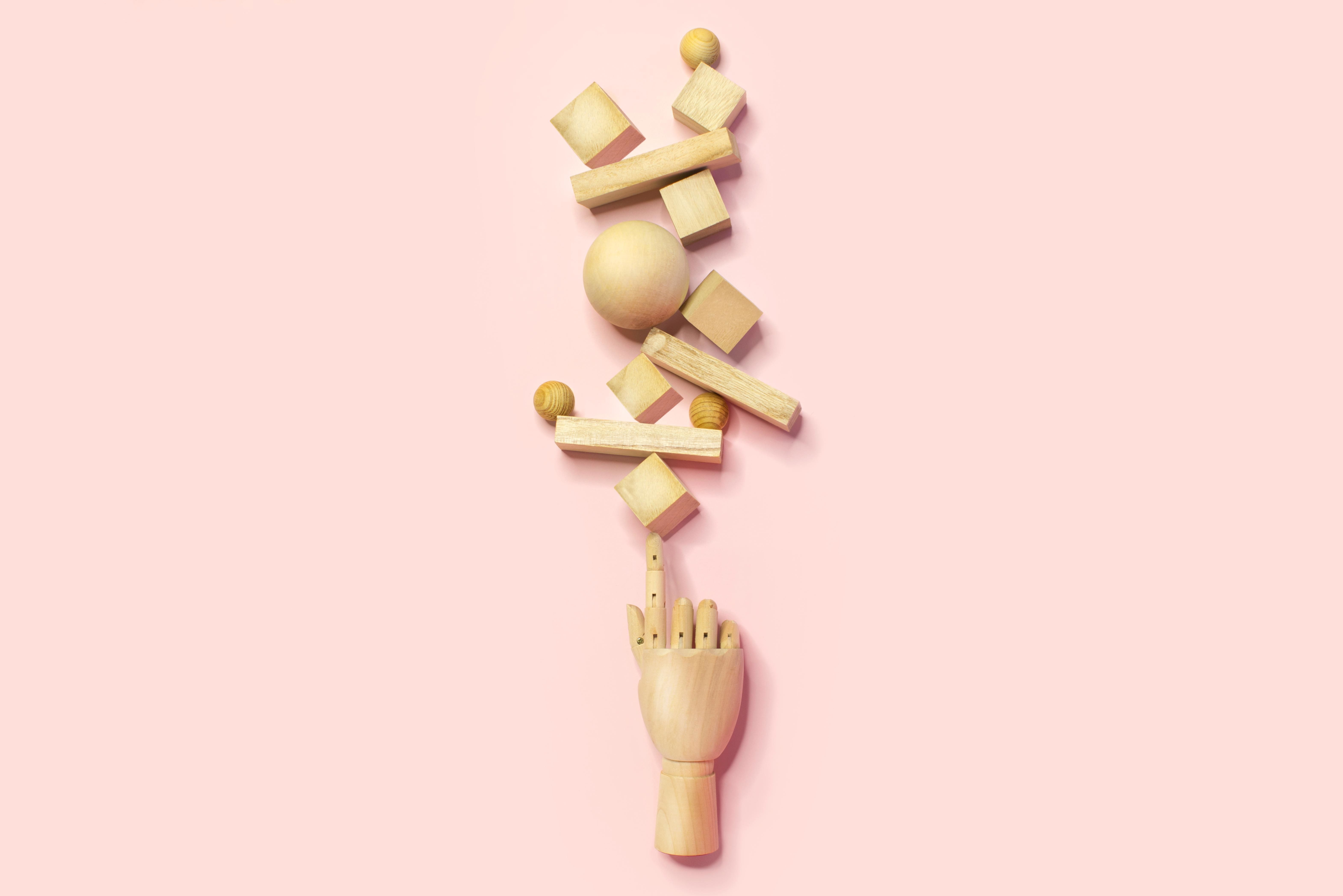 wooden hand balancing many different shapes and sizes blocks. multitasking concept.