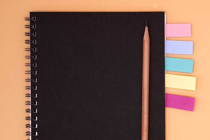 notebook with colored flags and pencil