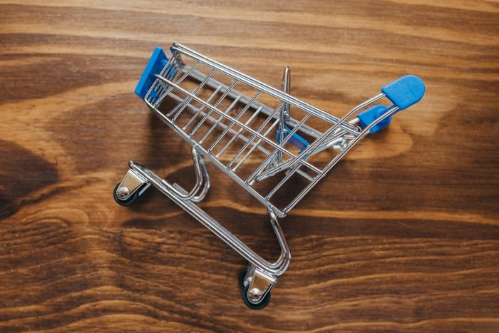 miniature shopping cart laying on wood desk background