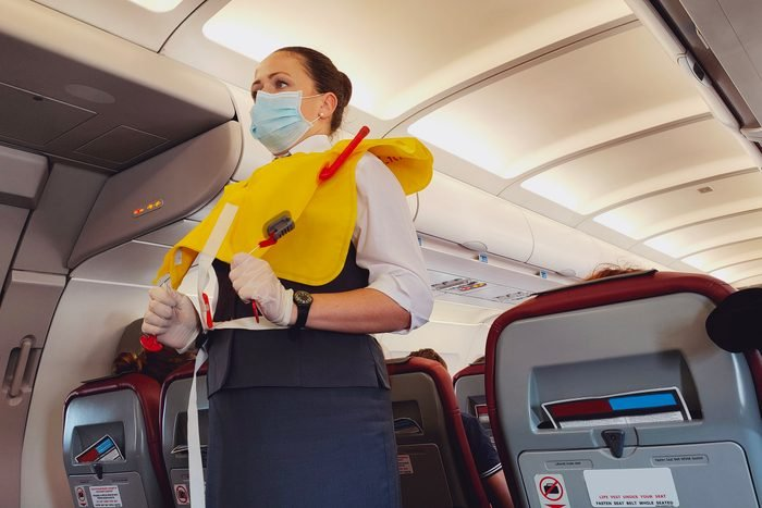 Low Angle View Of Cabin Crew Wearing Mask At Airplane