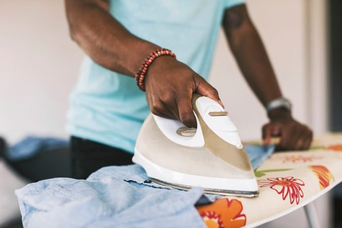 close up of man ironing clothing on ironing board at home