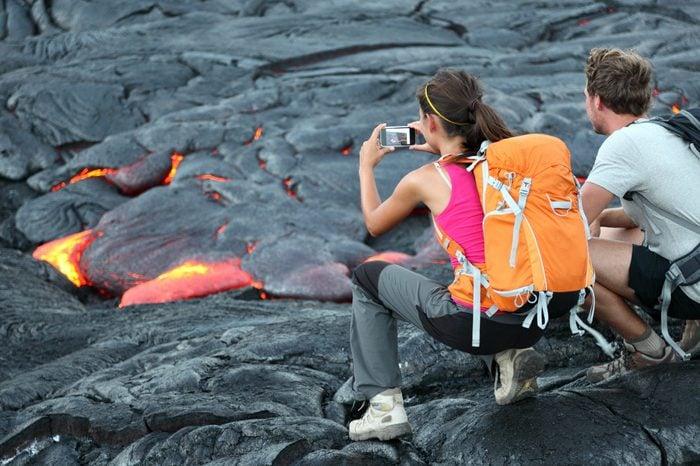 Hawaii lava tourist. Tourists taking photo of flowing lava from Kilauea volcano around Hawaii volcanoes national park, USA.