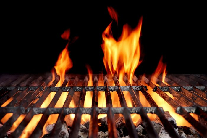 Hot Empty Charcoal BBQ Grill With Bright Flames On The Black Background. Cookout Concept.