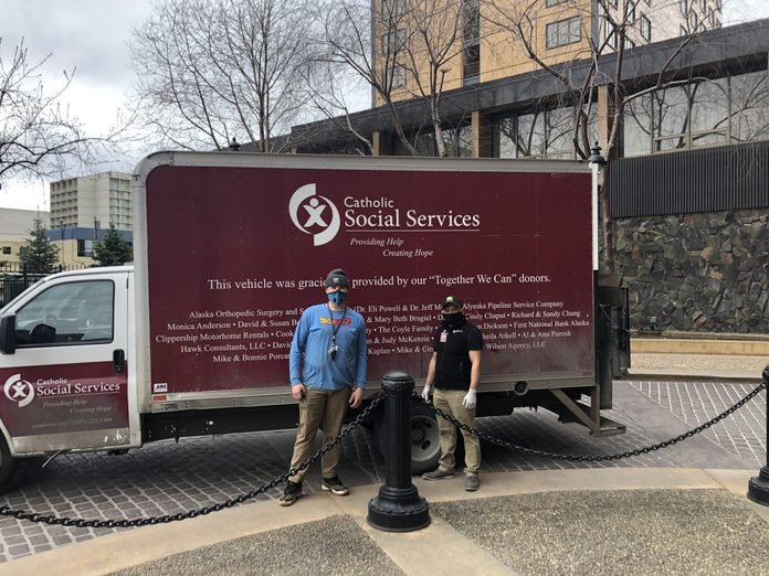 Catholic Social Services volunteers stand by their truck in Anchorage, Alaska