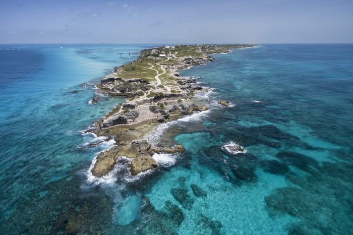 Isla Mujeres, Aerial View Punta Sur. Crystal clear turquoise water, waves crashing on the rocky shore, and the ruins of the temple of Ixchel.