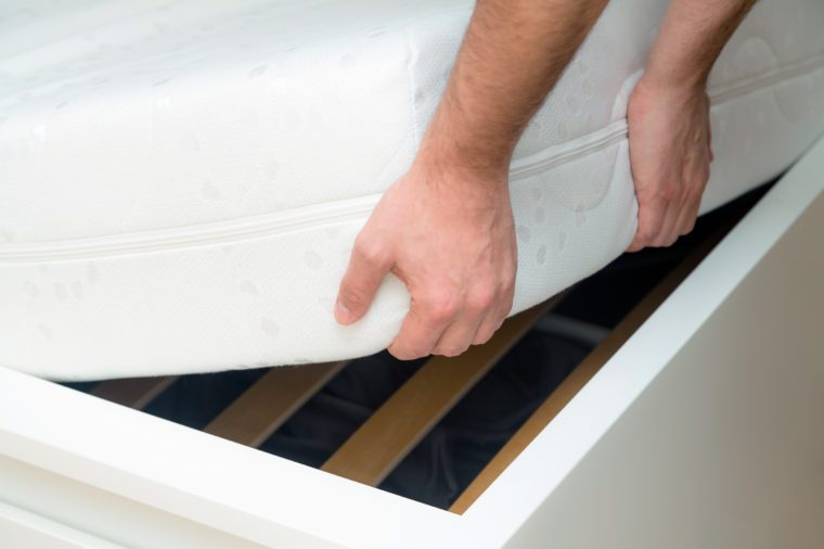 Man hands lifting the mattress at the bedroom. Looking at the bed frame, inspects the mattress