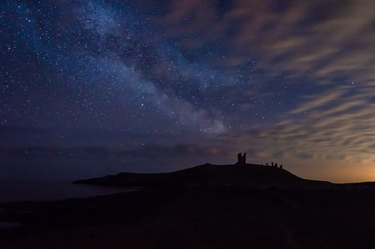 Milky Way above Dunstanburgh Castle, at night on the Northumberland coastline in England