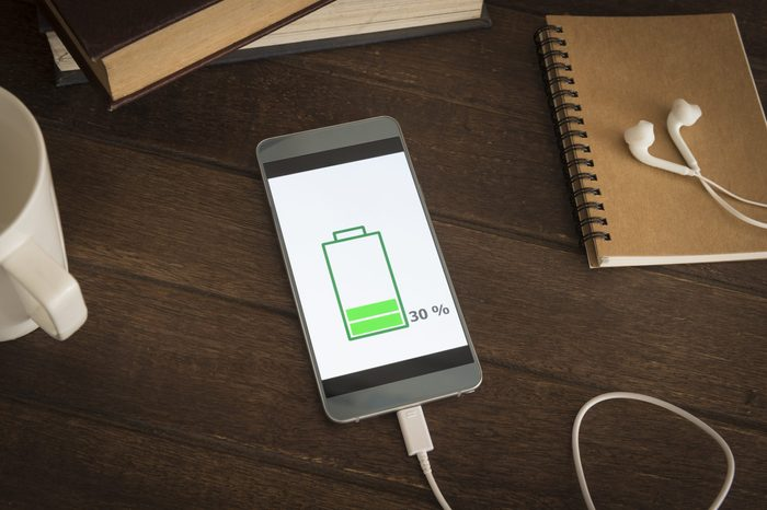 Mobile smart phones charging on wooden desk