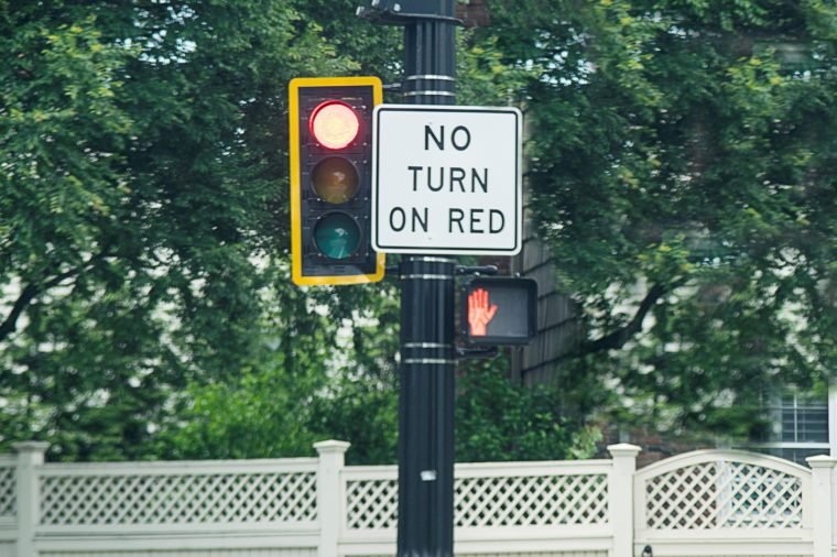 No Turn On Red Sign attached next to a traffic light pole made in rectangular shape paint in white and black color