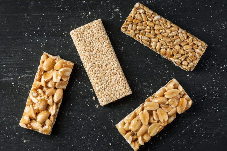 Peanut, sesame and sunflower seed brittle on a black wooden table, top view, flat lay.