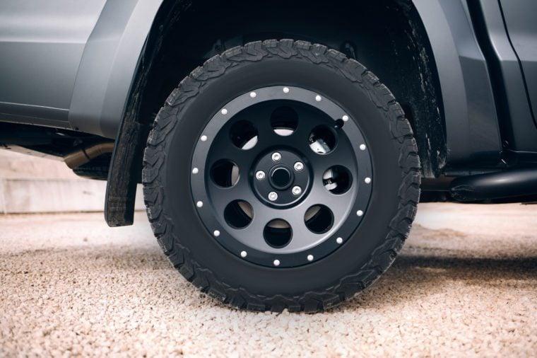 Suv car stopped at dirt road. Off road car wheel disassembly protection locked ring.