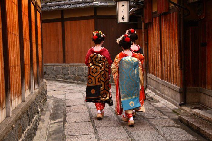Three geishas walking on a street of Gion (Kyoto, Japan)