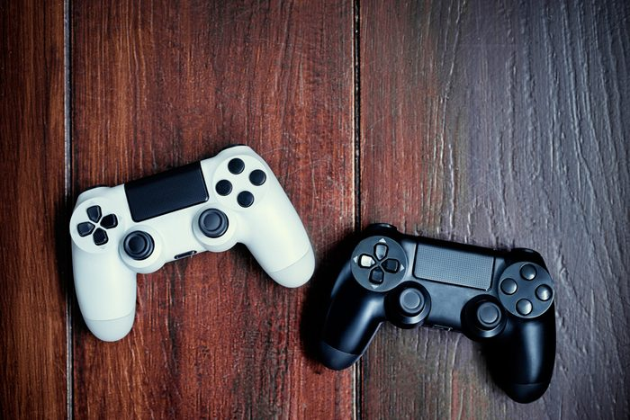 Video game competition. Gaming concept. White and black joystick on wooden background.