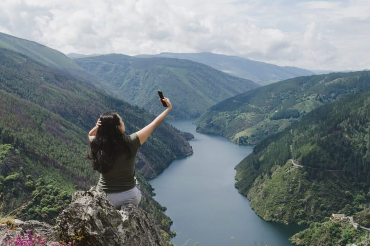 Woman taking selfie in a mountain landscape with river. View of the Salime reservoir from the village of Paisega in Pesoz, Asturias - Spain.