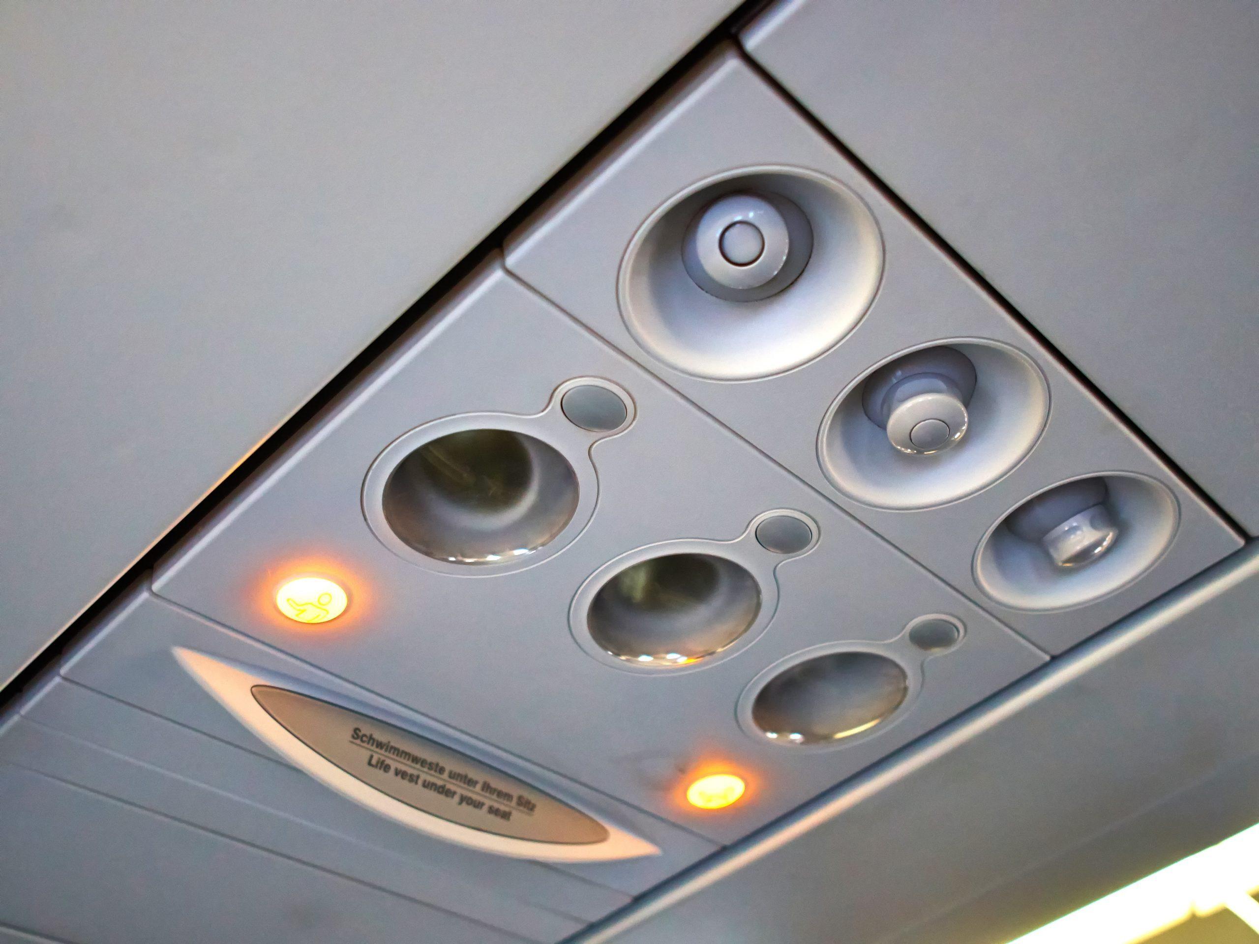 Passenger plane cabin overhead panelwith lights turned on