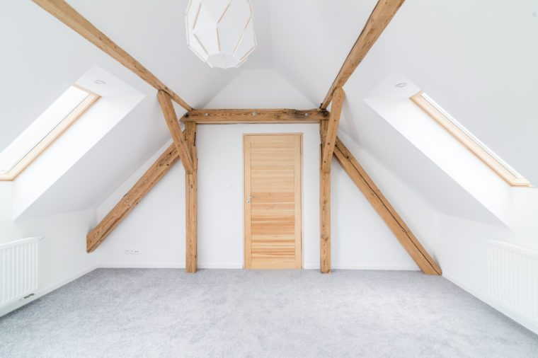 Empty attic room with wooden ceiling beams. Modern, bright attic apartment.