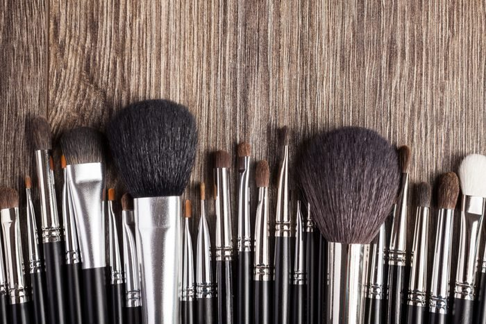 Professional make-up brushes on wooden background. Beauty industry