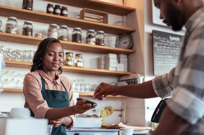 Customer using a bank card and nfs technology to pay a barista for a purchase at a cafe