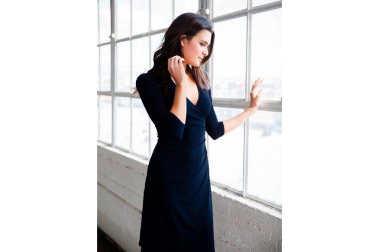 woman in a black wrap dress stands near a window