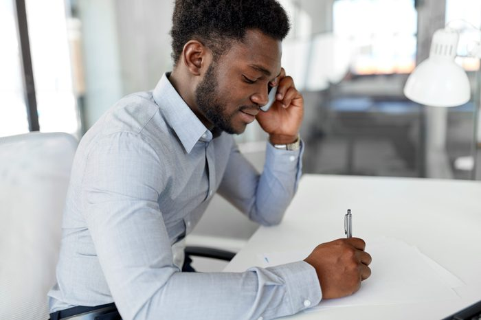 business, people, communication and technology concept - smiling african american businessman with papers calling on smartphone at office