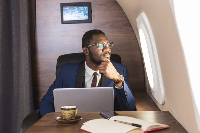 Attractive and successful African American businessman with glasses working on a laptop while sitting in the chair of his private jet.