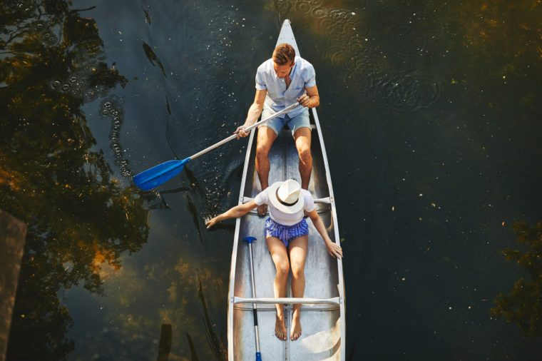 High angle of a young couple sitting in a canoe together paddling on a still lake in summer