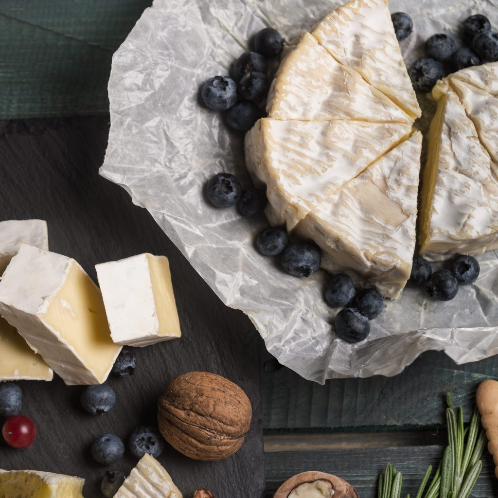 Tasting cheese dish with herbs and fruits on old black wooden table. Food for wine and romantic, cheese delicatessen. Menu design horizontal. Top flat view.