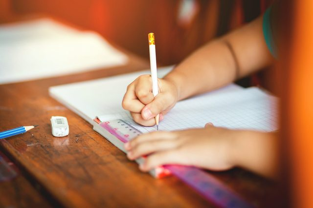Children's hands are doing their homework.