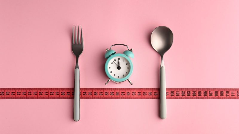 Composition with cutlery, measuring tape and alarm clock on color background. Diet concept