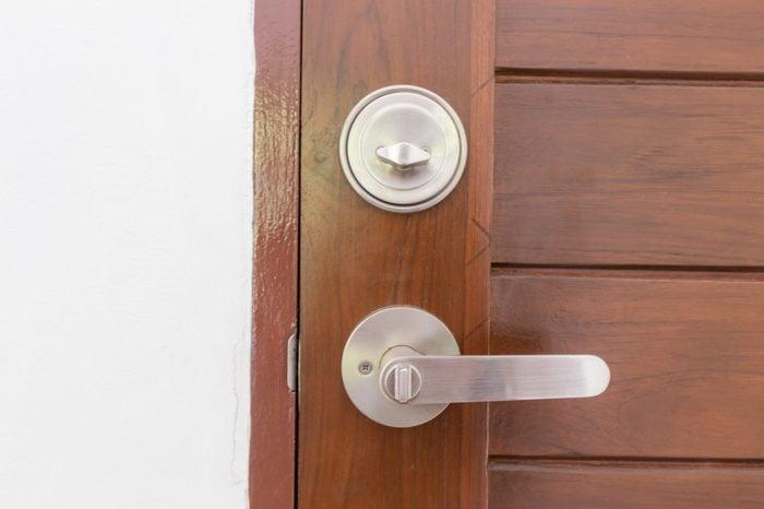 Modern stainless knob dead lock on teak wooden door, Interior object