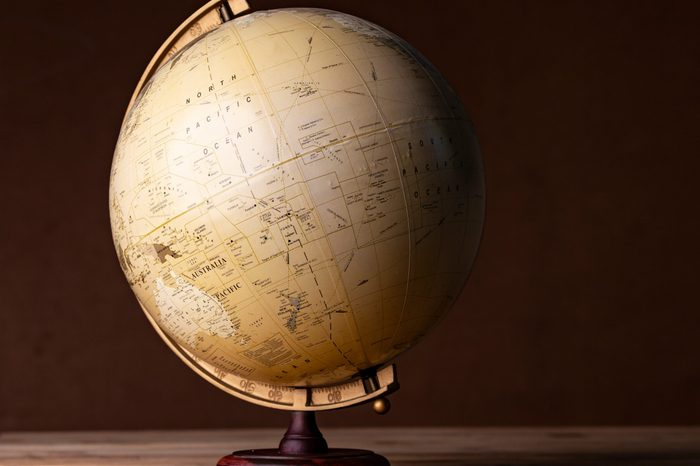 A world globe sitting on a wooden table