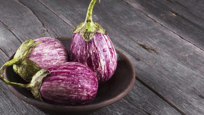 Harvest of eggplant graffiti on a dark wooden background