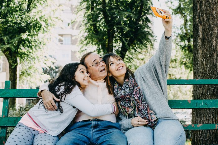 A father with his daughters sitting on a stone bench, taking themselves some photographs. Father's day. Relaxed autumn day in family outdoors. Lifestyle portrait.