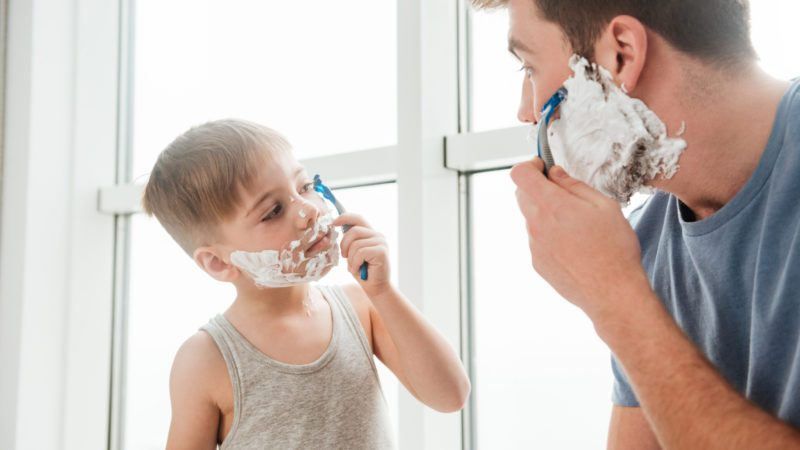 Photo of young happy father and son are applying shaving foam on their faces and smiling while shaving in bathroom