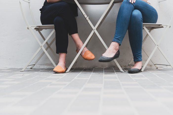 Lower legs of two women in relative friendship at outdoors office or restaurant. People and lifestyles concept.