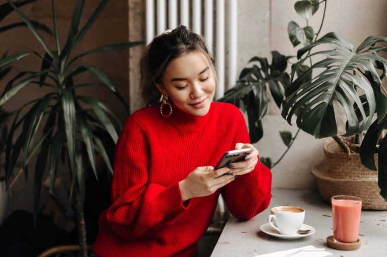 Charming young girl in massive earrings and bright sweater chats in phone while sitting in cafe over cup of coffee