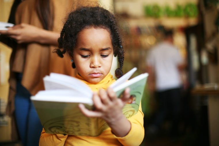 Cute little Afro-American girl in casual clothes reading a book.