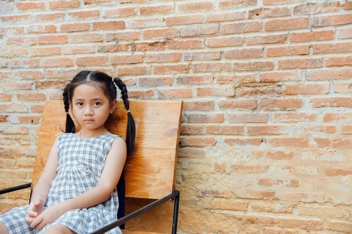 Little girl sitting on a chair with brown brick background