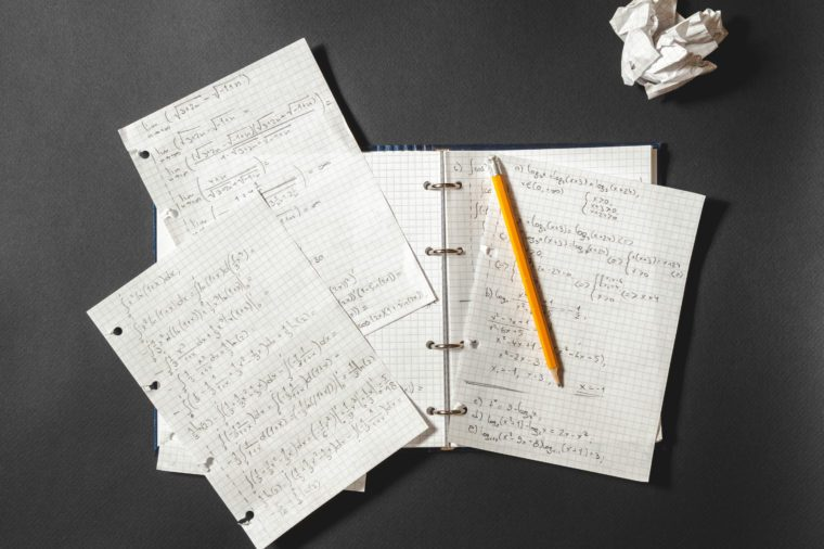 Solving a mathematical problem in a notebook. Crumpled piece of paper on black desk.