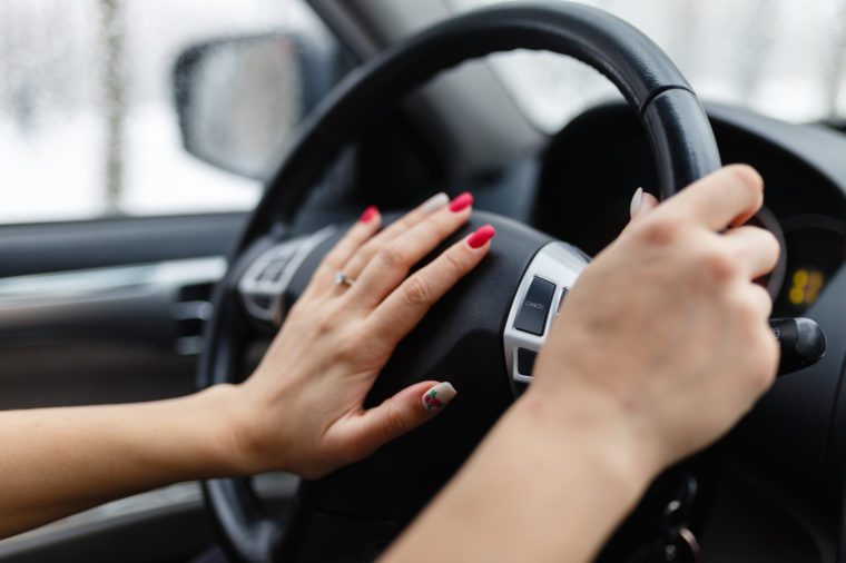 Close up of woman hand pressing the horn button while driving a car through the road. Woman driving a car with hand on horn button. Closeup woman hand holding steering wheel and honking the horn