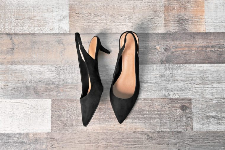Pair of female shoes on wooden background, top view