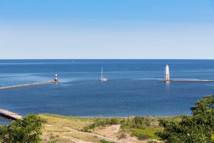 A sailboat passes between the Frankfort, Michigan North and South Breakwater Lights and into Lake Michigan on a bright and sunny morning.