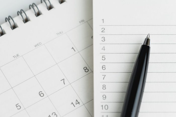 Writing to do list or work target plan concept, black pen on notepad with list of numbers on clean desktop flip calendar.